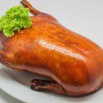 Close-up roast peking duck (Whole Duck) on white plate and white
